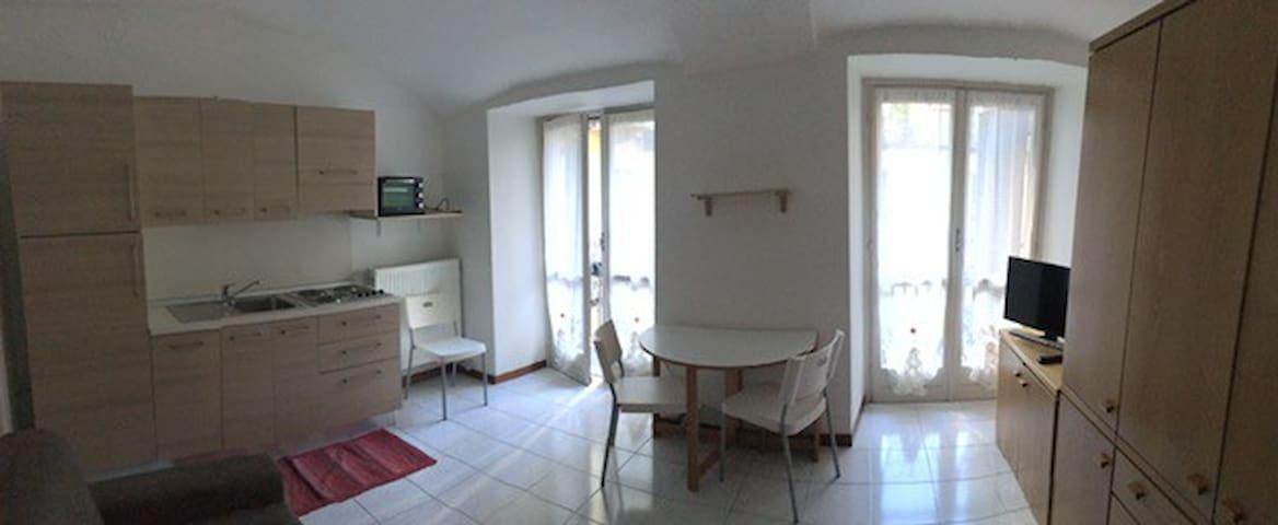soggiorno con angolo cottura, zona pranzo, con due porte finestre che escono sul balcone