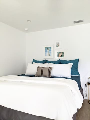 King sized bed with a super comfy mattress topper and all the linens and pillows you could ever need! View from pull out couch.