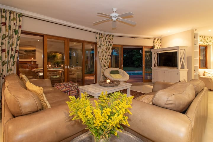 Lounge leading to patio and pool. Smart TV with PVR DSTV (record your programs).