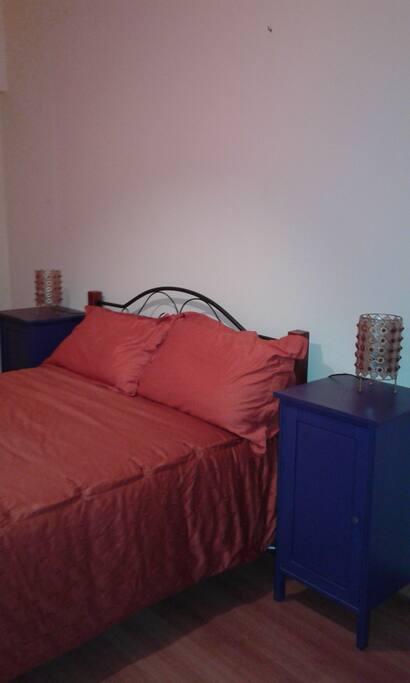 Quarto privado com cama casal e divã.