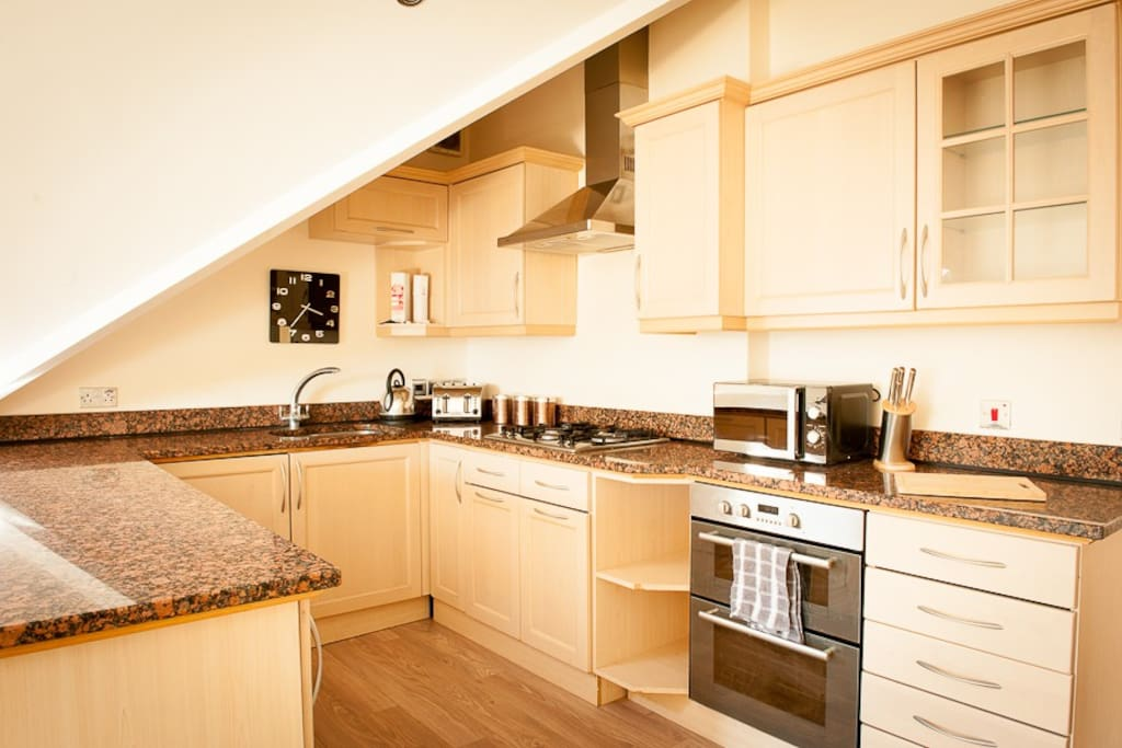 Fully equipped kitchen with dishwasher, washing machine, oven, hob and microwave.