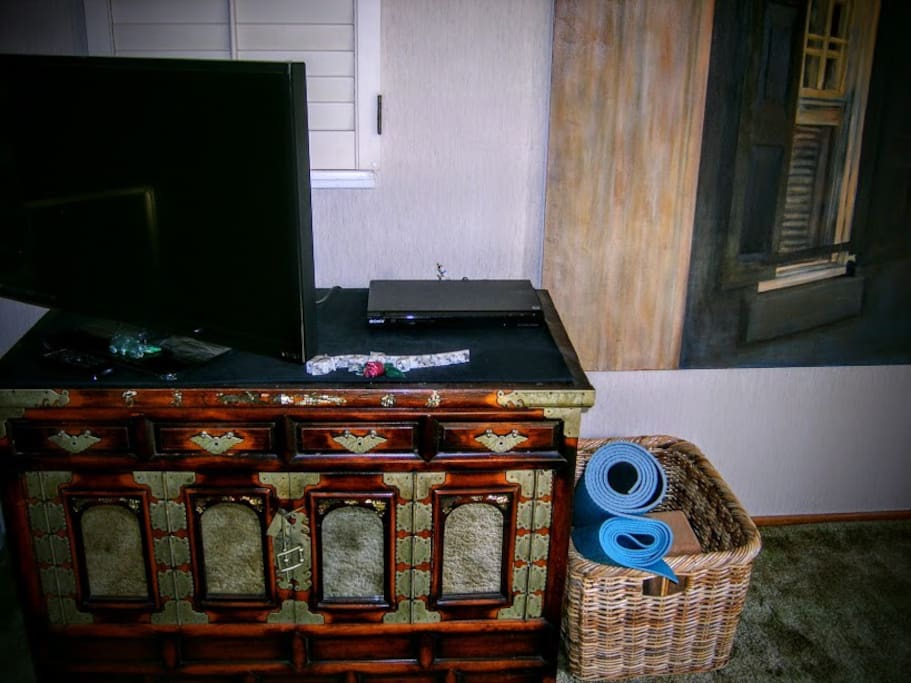 """30"""" x 18"""" TV on the Asian, antique chest and yoga mats."""