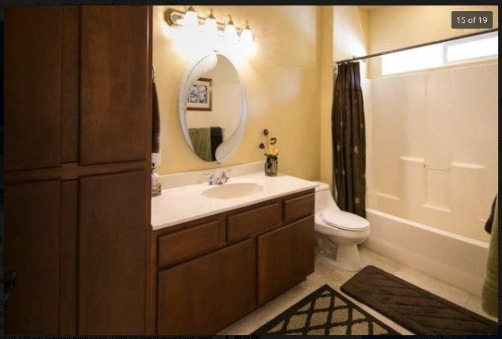 Well-lit shared bathroom with shower and fresh towels.