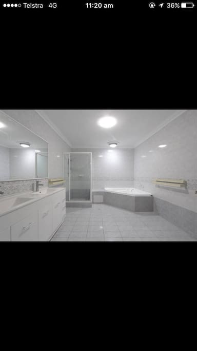 Your bathroom with double sink, toilet, shower and hot tub
