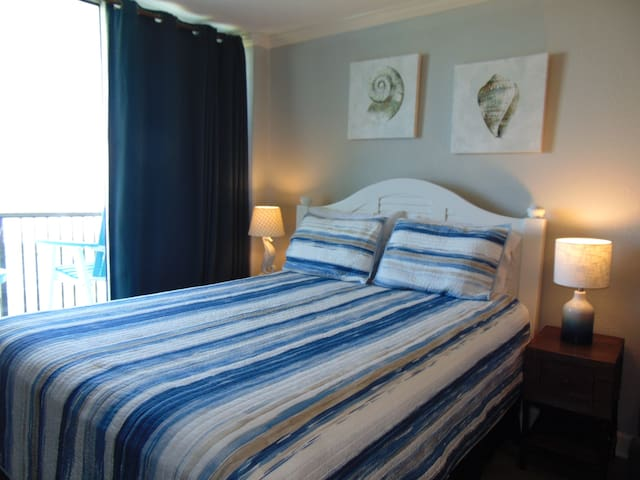 From the amazingly comfortable queen sized bed you'll have a view of the water (if you like) or close the black-out curtains for late sleepers - you are, after all, on vacation.