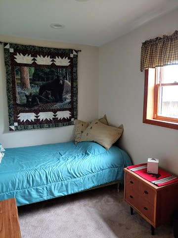 Third bedroom is a single bed, dresser, nightstand and small chest with extra bedding and tabletop fan.