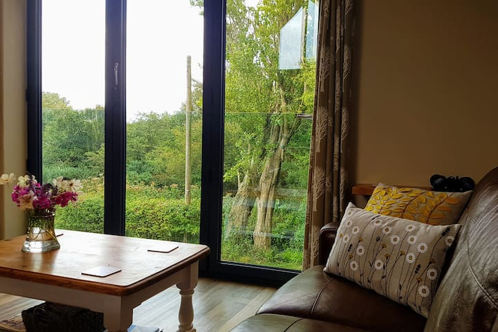 Lounge view onto Tree's and bird feeder great for watching the weather and wildlife. By-fold doors open fully with a glass balustrade beyond it really does bring the outside in