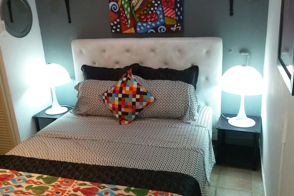 Queen size bed with designer sheets in air conditioned bedroom.