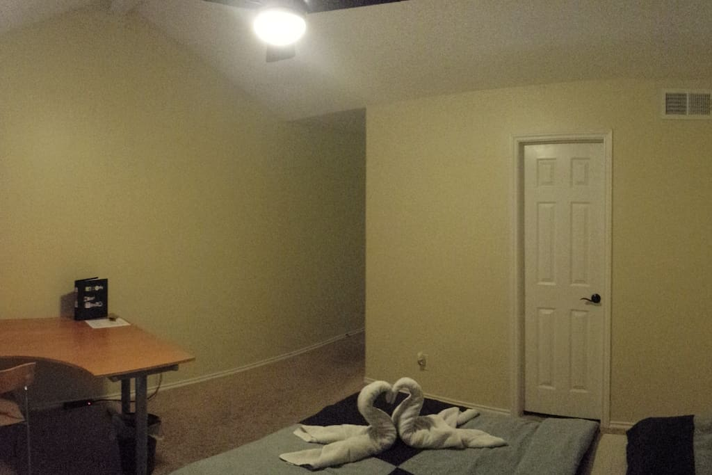 Fully furnished large bedroom with two closets and a desk.