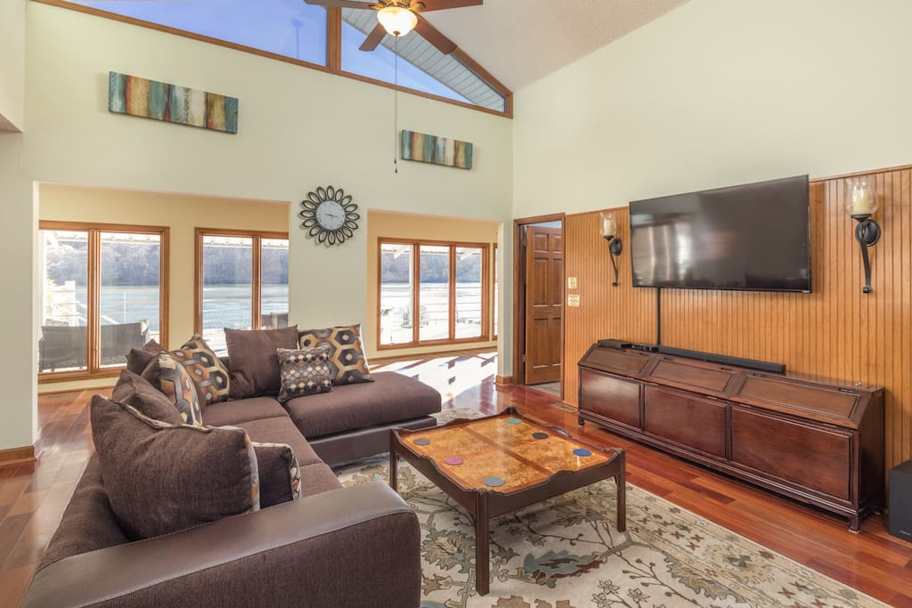 """Spacious living room with river views and 60"""" TV."""