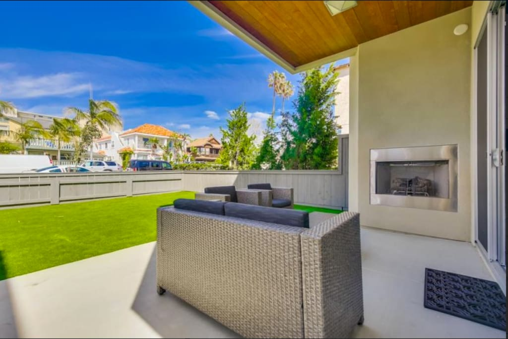 Ground floor patio, fenced in with artificial grass and patio furniture.