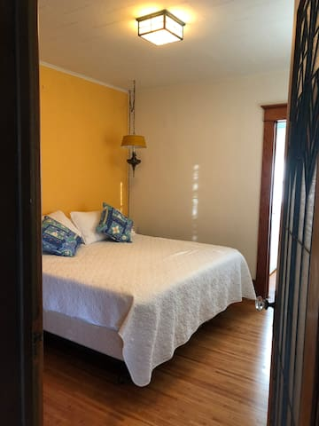 Master Bedroom w Kingsize bed, end tables, dresser with window. Incl stained glass door which leads to the 3 season walk in porch. Wake up, grab your cup of coffee and favorite book to start your day off with some quite time -just you and the birds