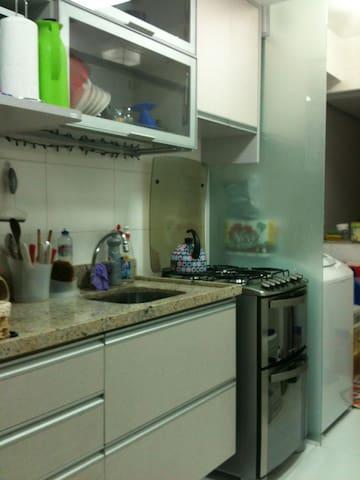 Cozinha equipada, com fogão a gás, forno de micro-ondas, geladeira e máquina de lavar roupas.