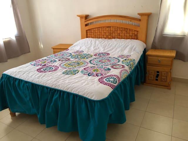 Amplia alcoba con cama para dos personas. Colchón y base de cama totalmente nuevos; respaldo y burós de madera labrada a mano con diseño de petatillo.
