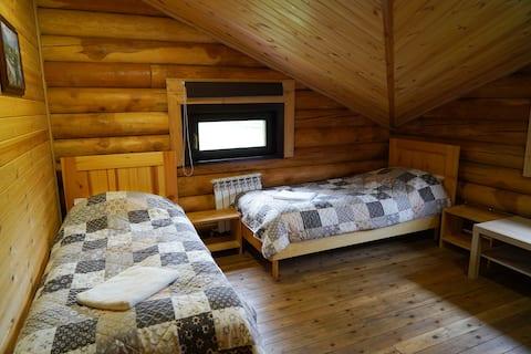 Кровать в трёхместном номере в доме из бруса