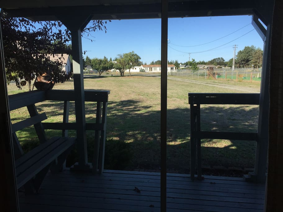View from sliding door; porch with bench and bistro set.