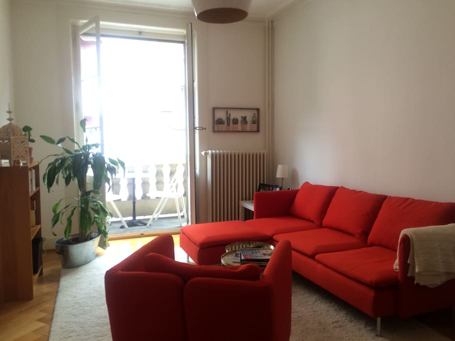 Large living room, with a balcony and a sofa wide enough for one traveller to sleep on.