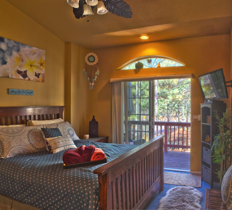 Queen bed with private deck outside, and flat screen, smart TV