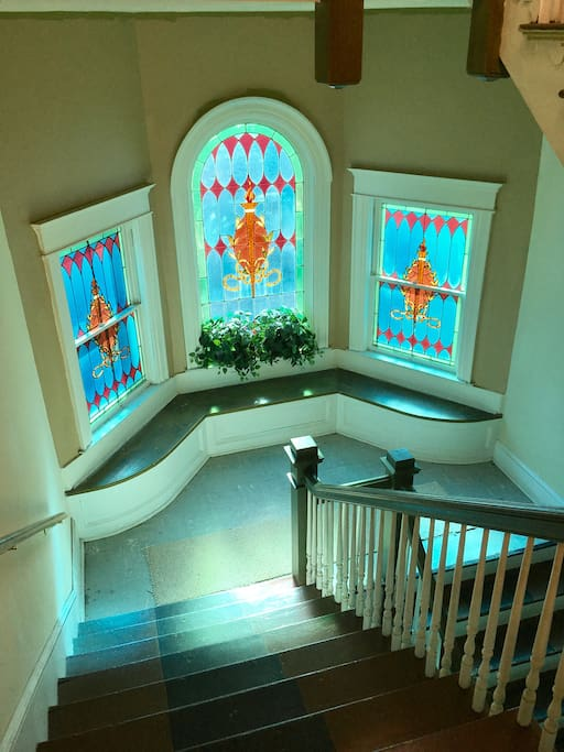 Staircase with beautiful stain glass windows.