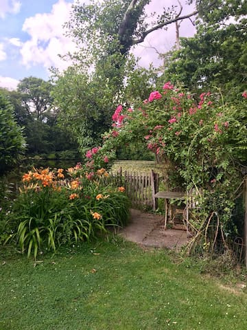 Rose arbour over guests patio beside lake for a welcome cup of tea, glass of wine or a picnic