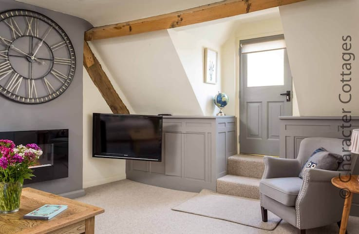 The living room has comfortable seating and a cosy fireplace