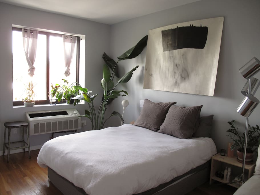 Bedroom with queen size bed, corner lounge chair, a closet, and plants + light