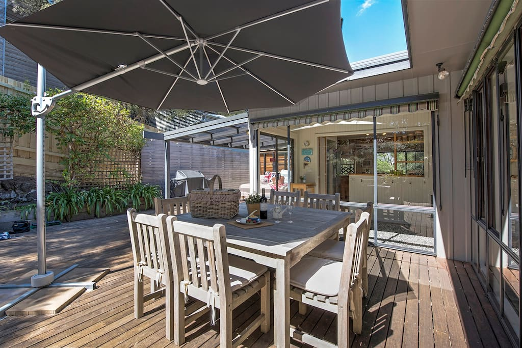 Under the large outdoor umbrella and window awnings - you can enjoy entertaining at the BBQ and dine outdoors