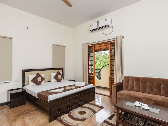 Spacious, private Studio with Couch seating and extra long bed with noiseless Split AC, Flat screen TV and attached Balcony. It also has its own individual, fully-equipped Kitchenette.
