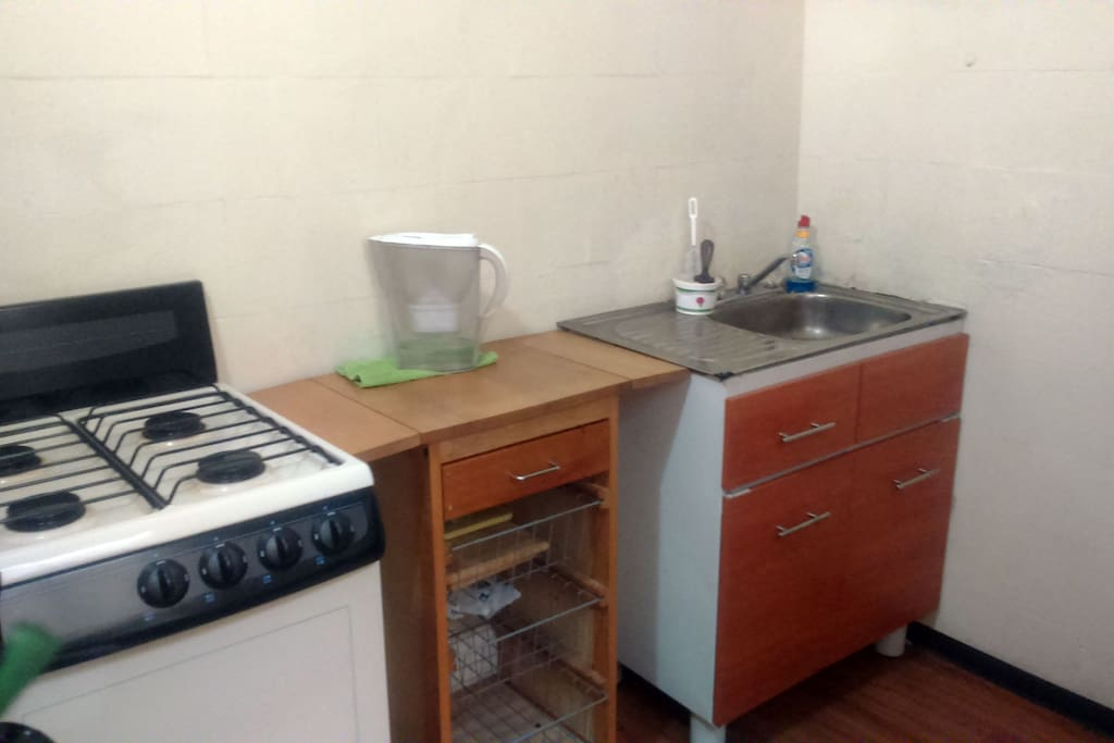 Kitchen with microwave, coffee maker, stove, mini oven and assorted tools