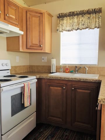 Fully equipped kitchen with coffee maker, pots, pans, skillets, toaster and range.