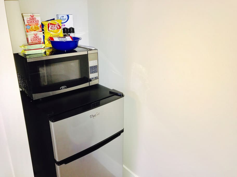 Mini kitchenette with fridge, freezer, microwave, and complimentary snacks and beverages.