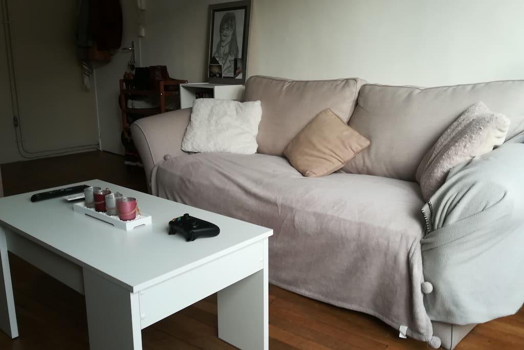 Canapé avec une table basse possédant un plateau relevable.
