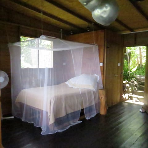 The bed with its mosquito net on a frame and window looking up the west coast of Saint Lucia