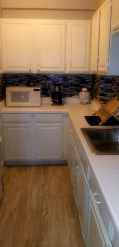 Kitchen with backsplash, microwave, stove & refrigerator.  There is no dishwasher or garbage disposal, as it is a 100-year old building .