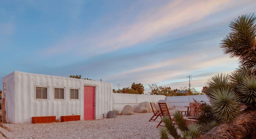 The guest shipping container shown here boasts two beds and a fully functional bathroom (shower, toilet and sink).