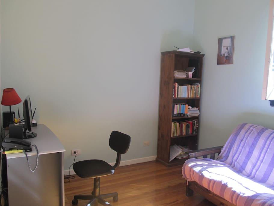 Dormitorio en el primer piso con sofá cama, escritorio y biblioteca. First floor's bedroom with bed/couch, desk and book chelfs