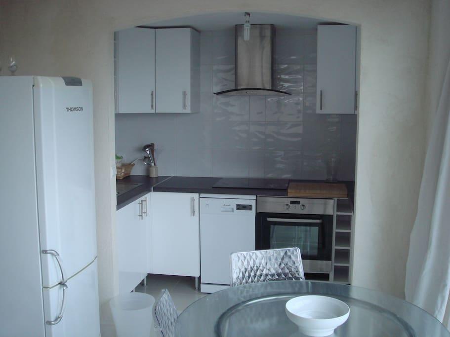 vue de la cuisine équipée avec plaque vitro, four, lave vaisselle, micro-onde et vaisselle, et casseroles