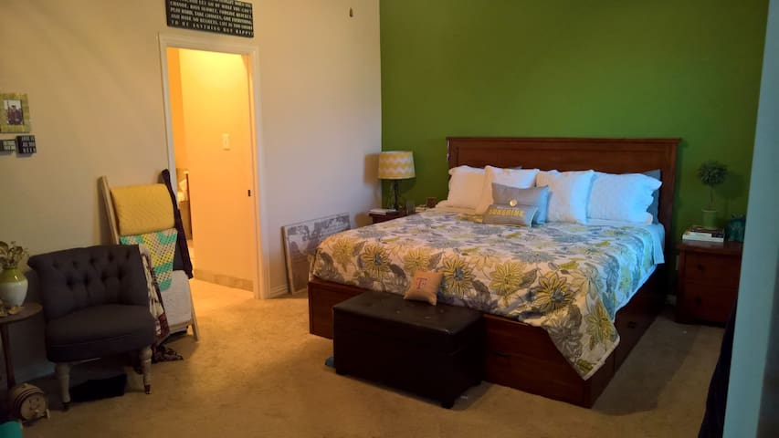 Master bedroom with king bed and large attached bathroom.