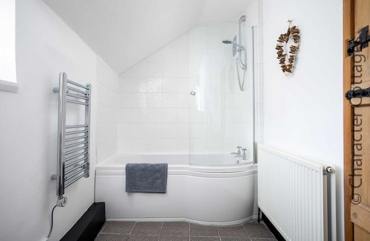 The family bathroom contains a bath with an overhead shower, toilet, wash basin and a heated towel rail