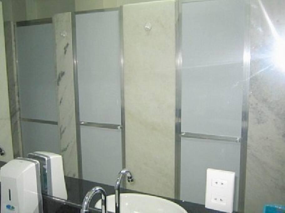 Banheiro coletivo com  3 box, 2 lavabos e 2 sanitarios, banheiro comodo e bem organizade