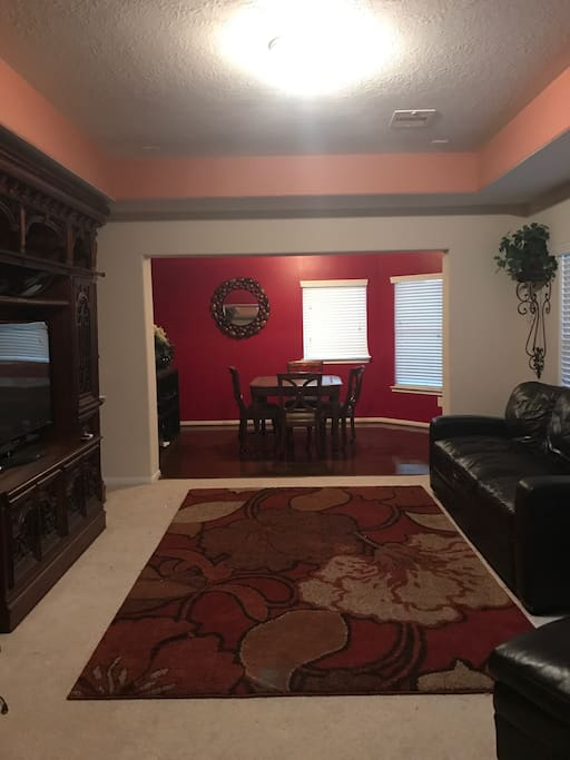 Large private living room with theater sized television and gaming/study/office area