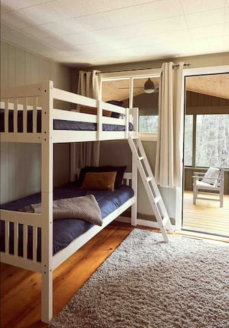 Bedroom 3 with bunk beds and door to the screened-in porch