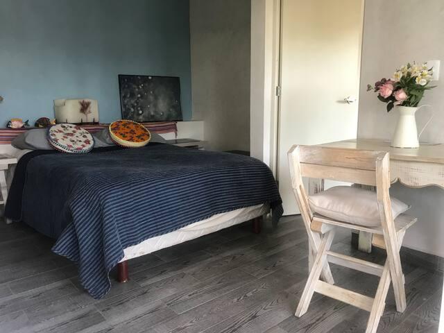 Recamara principal con cama matrimonial y espacio de trabajo