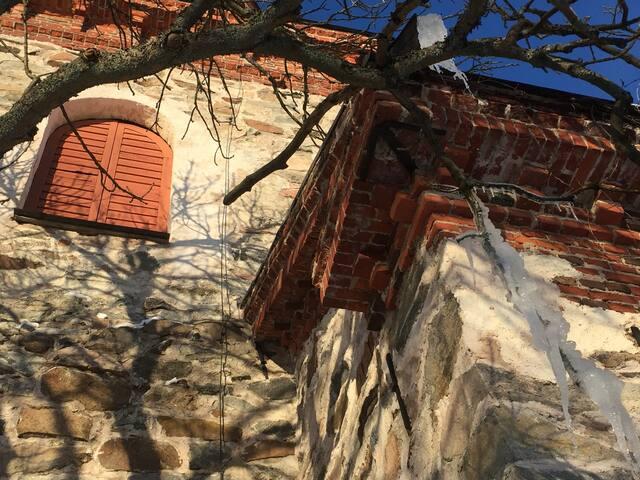 Kevätauringon muovaamia jääpuikkoja kirkon köynnöksissä. Kelloja soitetaan käsin. Sunnuntaisin luukut avataan ja koko kylä kuulee kutsun jumalanpalvelukseen.