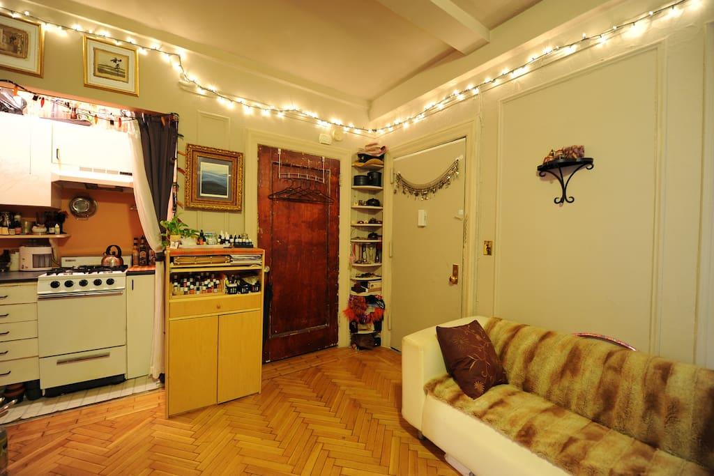 half of kitchen, closet, front door and couch
