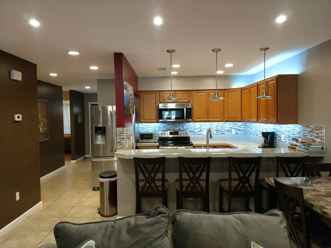Kitchen with Bartop and all stainless steel appliances.