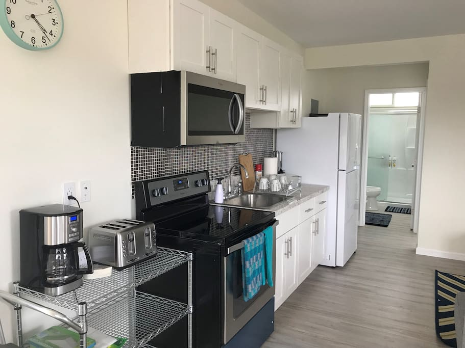 Full Kitchen with refrigerator, ice maker, microwave, oven, stove top, coffee maker, coffee grinder, toaster, ninja blender, rice cooker, electric kettle.