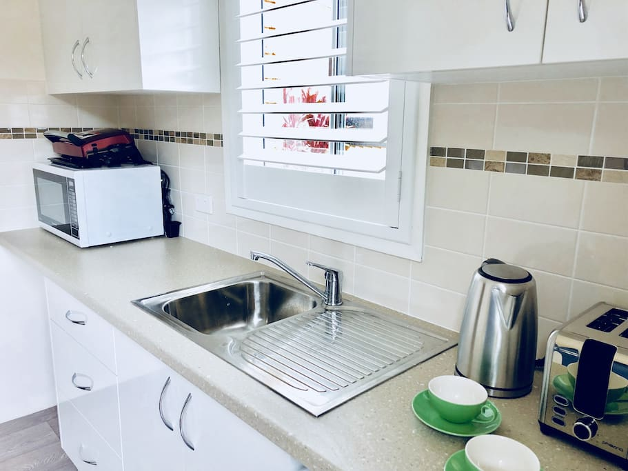 Kitchen/laundry with microwave oven, grill, kettle, toaster and washing machine.
