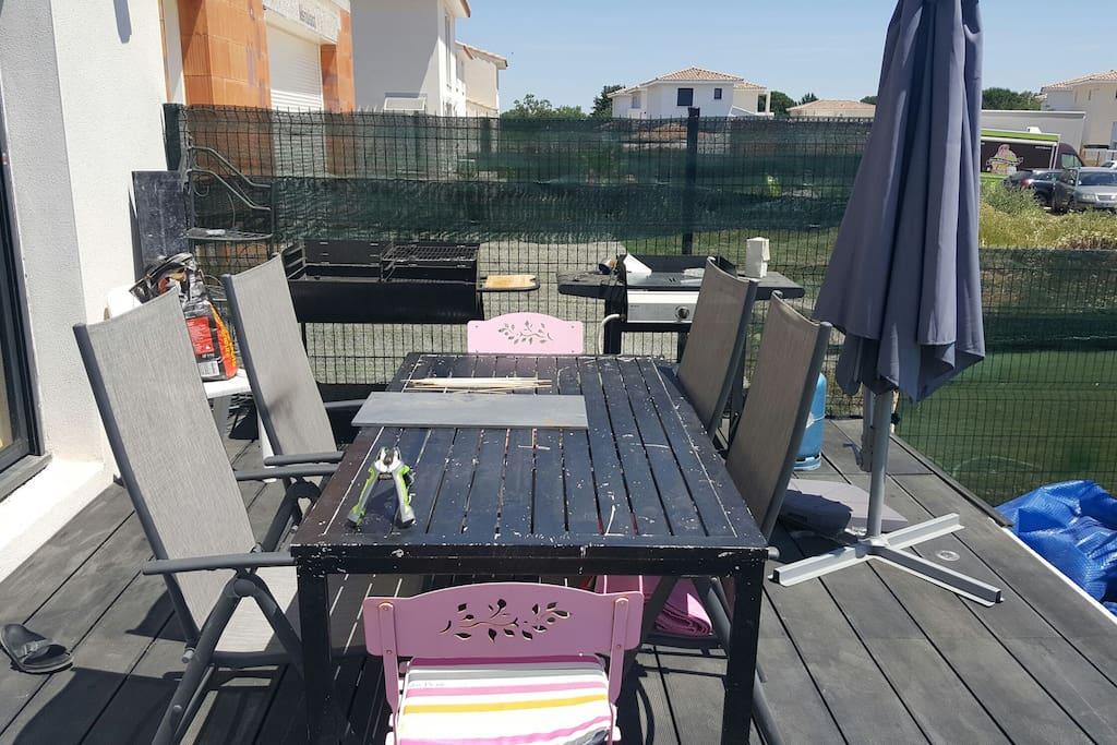table avec chaises de jardin, barbecue à charbon de bois et plancha à gaz