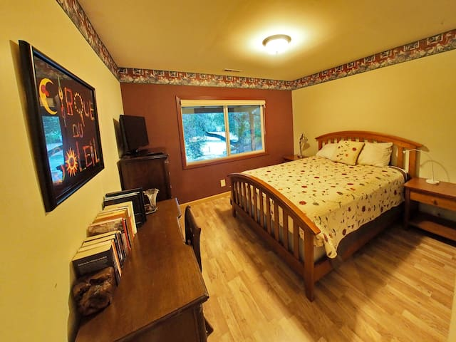 Bedroom/office with queen bed, desk, dresser, tv